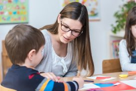 teacher working with preschool student at a table
